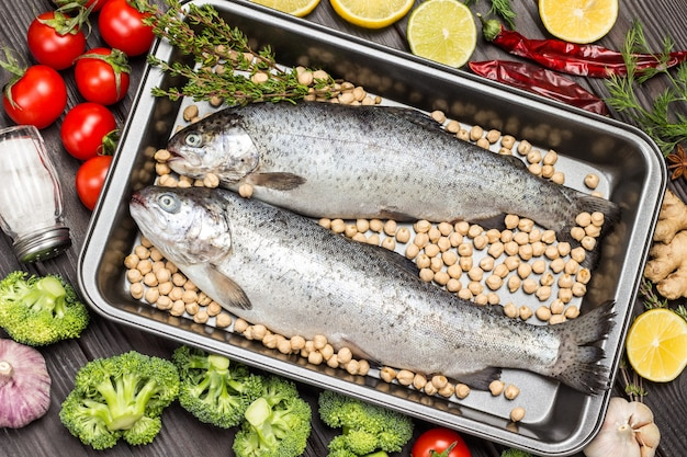 Fish trout with chickpeas in metal tray. cauliflower, lemon, pepper on table. flat lay