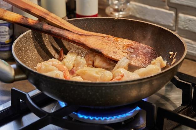 Рыба с грибами и креветками обжаривается в масле на сковороде, пошаговый рецепт из интернета.