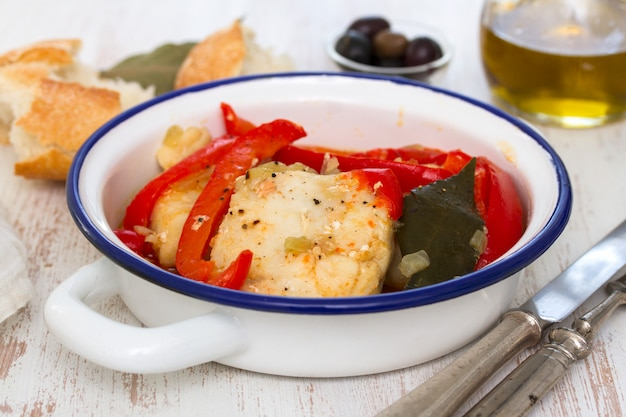 Fish with pepper on dish with bread and oil