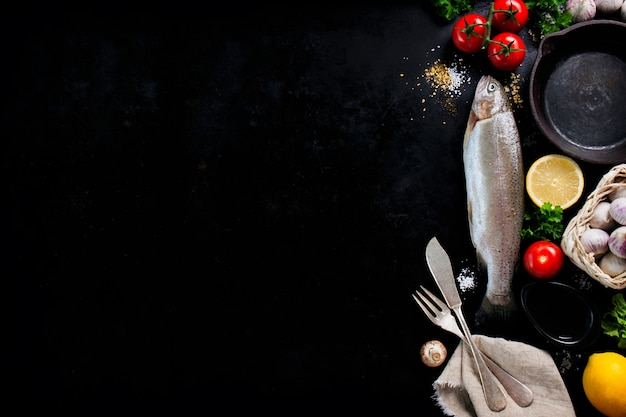 Рыба с овощами и столовые приборы на черном фоне