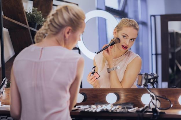 フィッシュボーンブレード。大きな光の鏡の近くに座って化粧をしている魚の骨の三つ編みのブロンドの髪の女性
