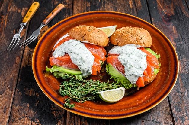Фишбургер с малосольной рыбой, лососем, авокадо, булочкой для бургеров, горчичным соусом и салатом айсберг.