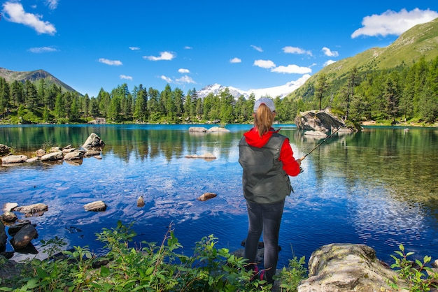 Fisher girl in an alpine lake
