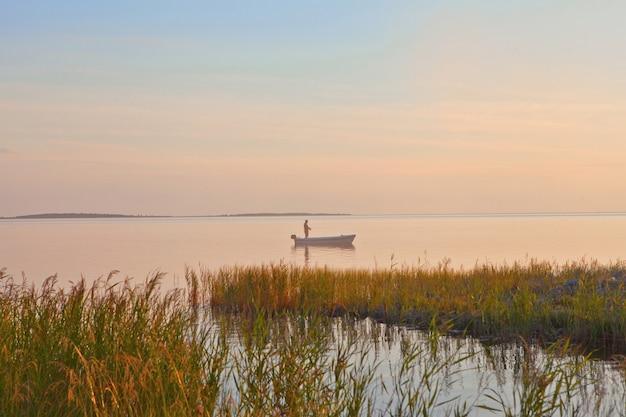 青とピンクの色でボートの空のピンクの夕日の海のシルエットのボートで漁師