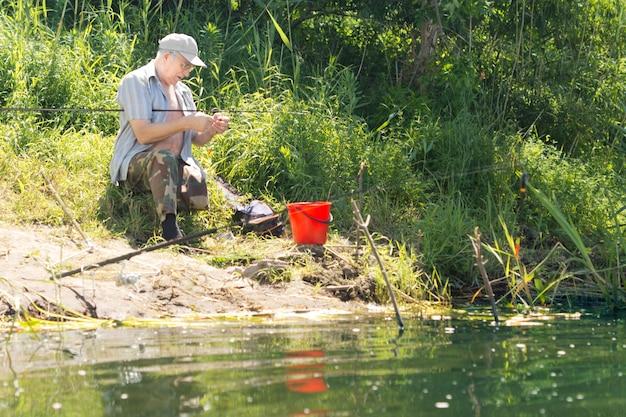 湖畔でフックを餌にする漁師
