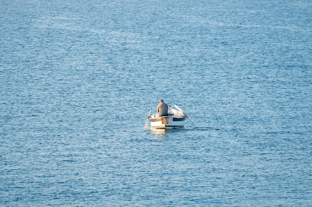 Fisherman in a boat fishing in the early morning. mediterranean sea. italy.