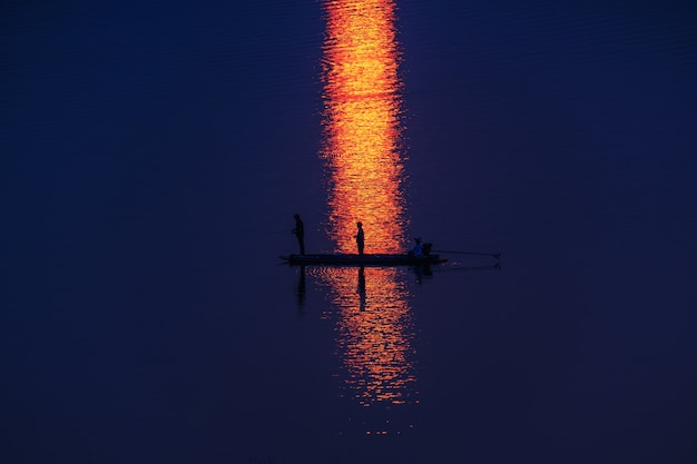 Fisherman on boat floating in lake,silhouette and reflect sunlight