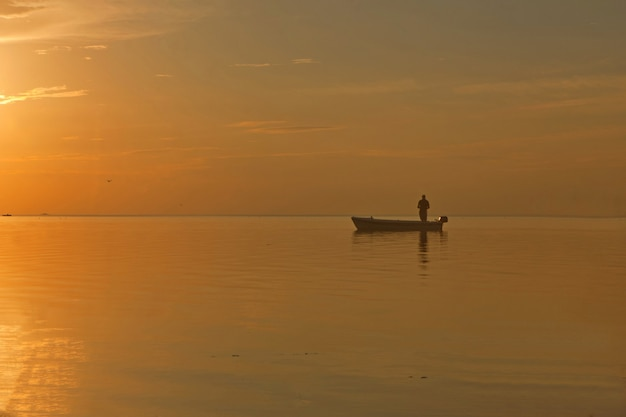 Fisherman at the boat on golden sunset sea beautiful and romantic sunset silhouette with boat