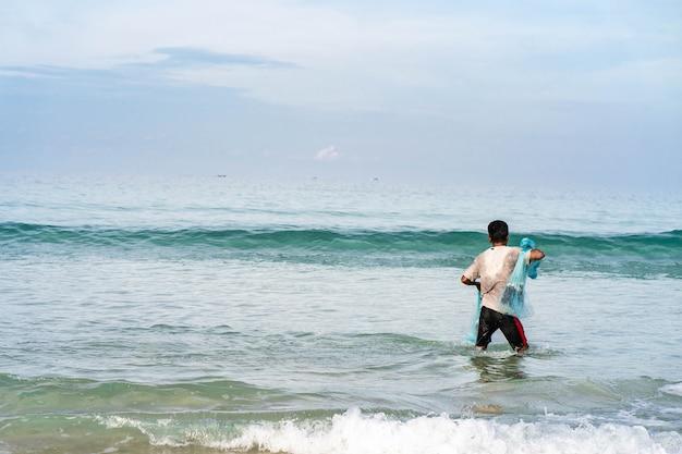 漁師は浜辺で網を投げた。