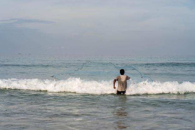 Рыбак закидывает сеть на пляже.