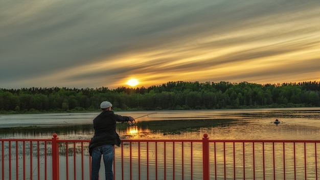 A fisherman catches fish from a bridge at sunset recreation on the lake