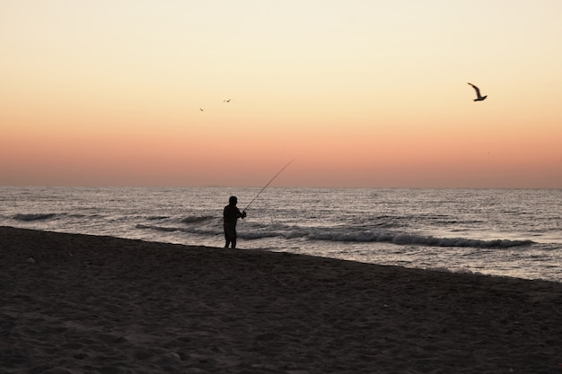 Fisherman catches fish from the shore at sunset