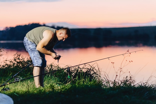 Fisherman catching carp at lake in summer time at evening