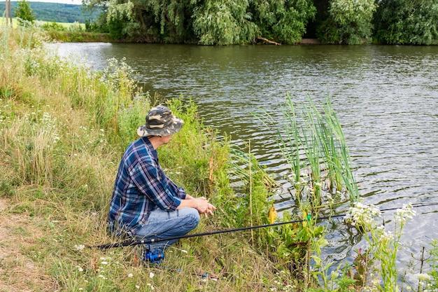 湖で釣りをする漁師、静かで穏やかな夜に釣り竿を持って水の近くで釣りをする漁師