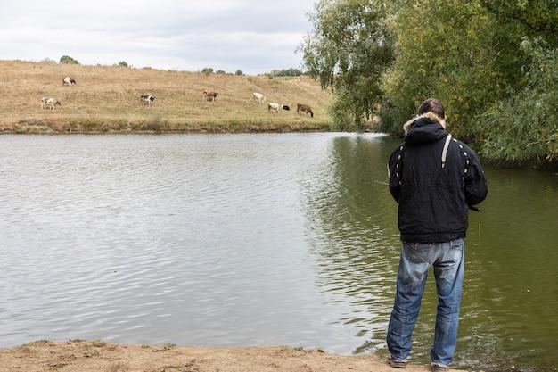 Рыбак ловит рыбу на озере, рыбак у воды с удочкой в тихий спокойный осенний вечер