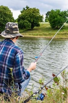 湖で釣りをする漁師、釣り竿で水の近くの漁師