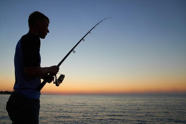 漁師は日没時に湖のシルエットで釣ります