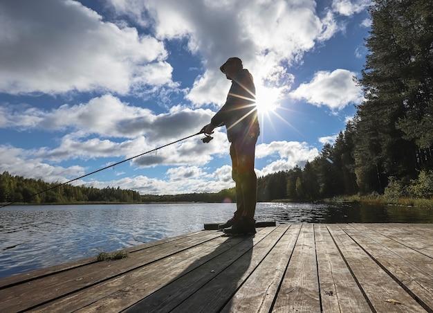 Рыбак, ловящий рыбу в одиночестве с удочкой и солнцем