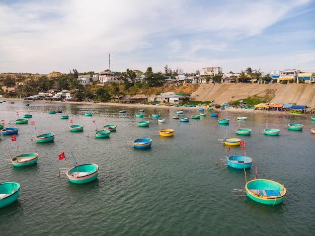 ベトナムの漁村にある漁師の漁船、カラフルな伝統的な漁船がベトナムのムイネーに停泊しました。上面図。航空写真