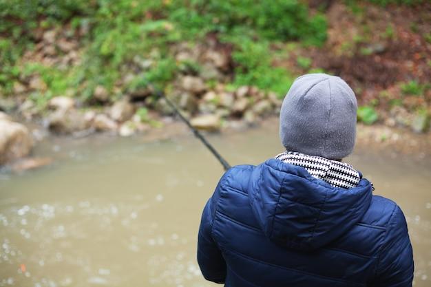 Рыбак, ловящий рыбу у реки осенью