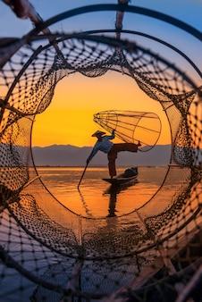 Рыбак рыбалка во время заката в городе янгон
