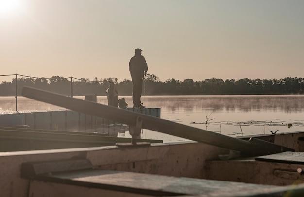 Рыбак, ловящий рыбу в туманное утро, силуэт человека, отдыхающий с удочкой на реке или озере в тумане