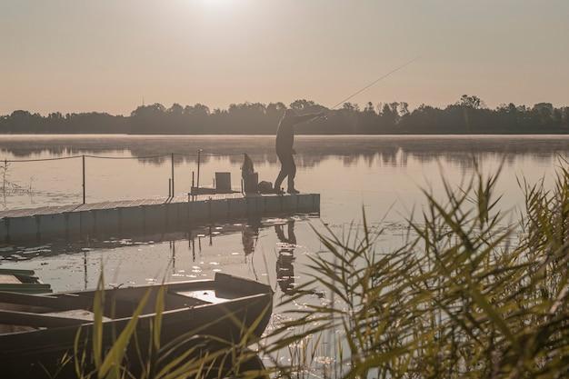 霧の朝の男のシルエットで釣りをしている漁師は、霧の中で川や湖のロッドで休んでいます