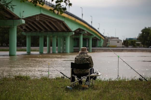 Рыбак ловит рыбу на удочку на берегу реки на мосту
