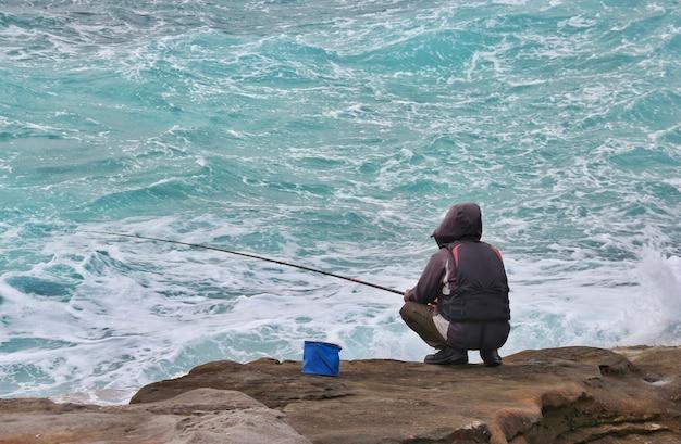 A fisherman fishing on rocks stone near ocean waves.