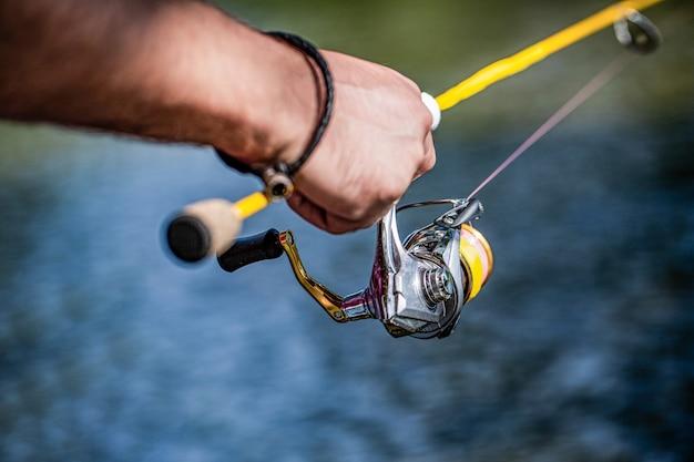リールで釣り竿を保持している漁師の手。釣りリール。アルミボディスプール付き釣り竿。釣り道具。魚の供給と設備。川の背景にある釣りリールのクローズアップ。