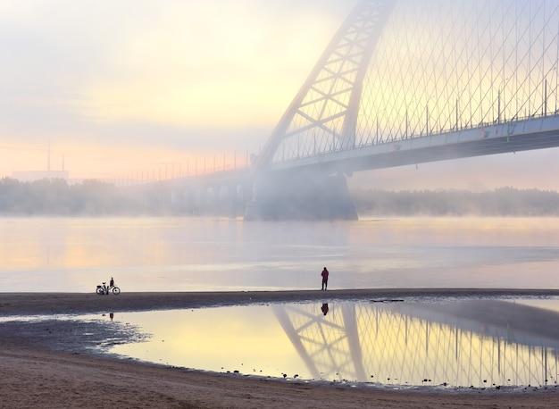 Рыбак у бугринского моста в утреннем тумане новый автомобильный мост через обь