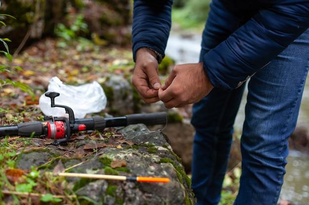 Рыбак держит приманку осенью