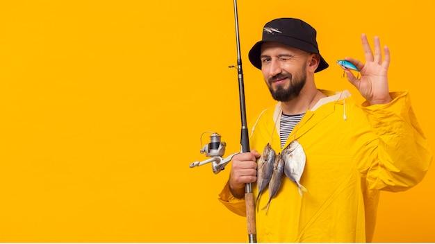 Рыбак держит удочку с приманкой