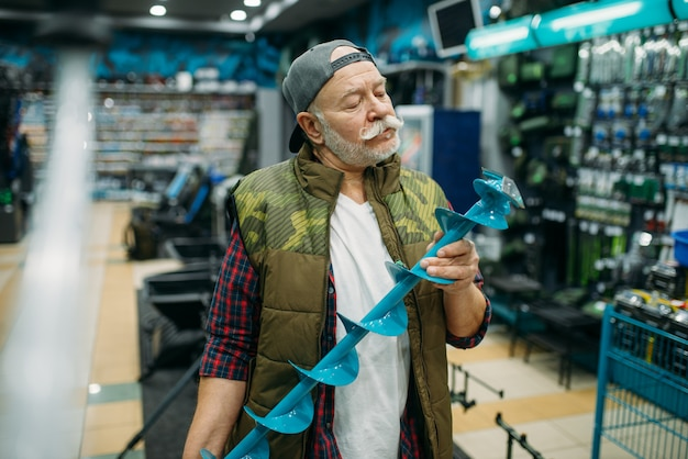 Рыбак держит сеялку для зимней рыбалки в магазине