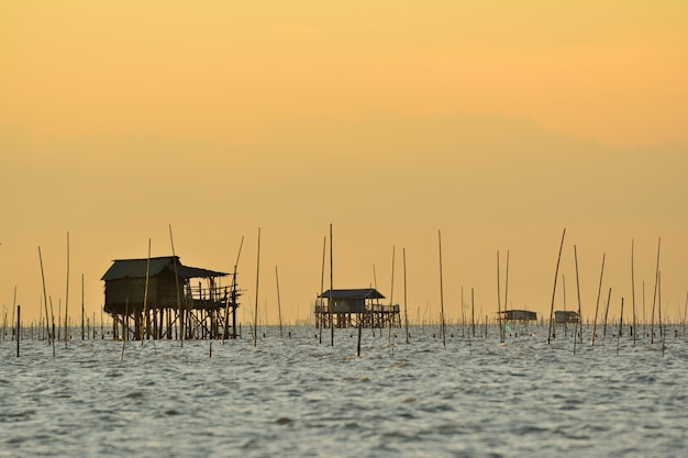 Fisherman  house on the sea with shellfish farm sunset background in thailand