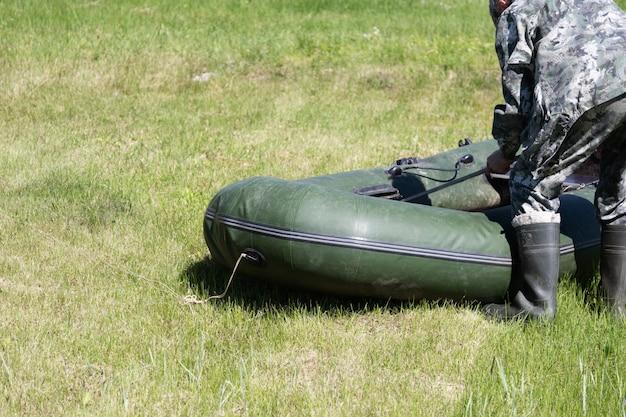 カモフラージュスーツと高いゴム長靴の漁師が草の上に膨脹可能なボートを折りたたむ