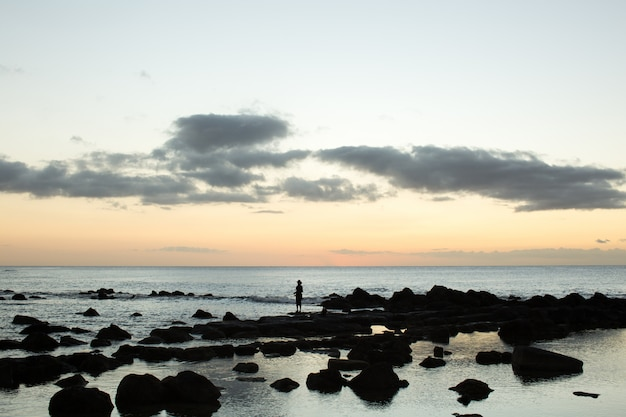 A fisherman is fishing in the black stones in the ocean.