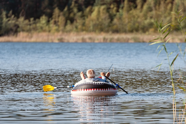 A fisherman is fishing on fishing rods from a rubber boat with oars, forest on a blurred background