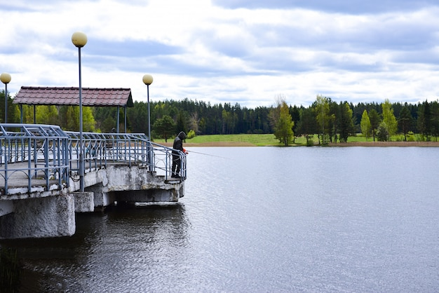 A fisherman is fishing on a lake from a concrete pier