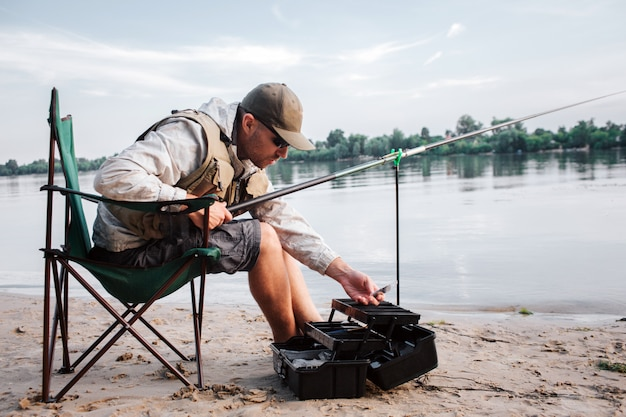 Fisherman is sitting in folding chair and leaning forward to opened black plastic box. guy holds fly rod and plastic bait in hands. it gets chilly outside.