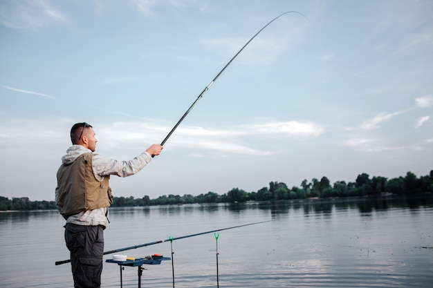 Fisherman is standing near watr and holding fly rod with right hand. he has it up really high. man looks straight forward. another fish rod is lying in hook.
