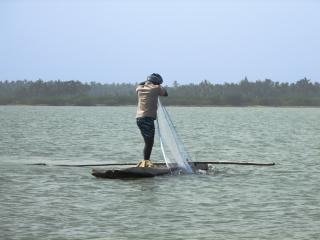 Fisherman in a log boat, backwater