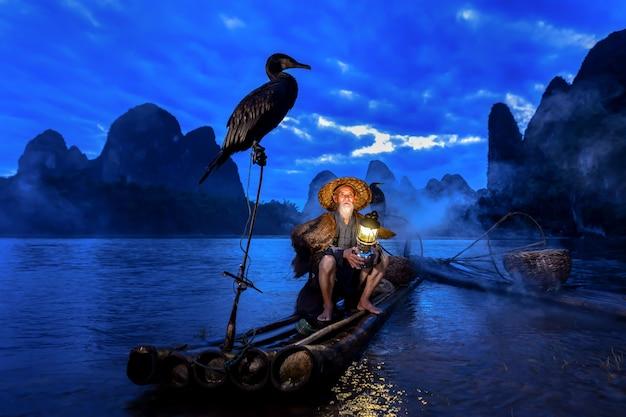 中国広西チワン族自治区の夜明けの青い時間の間に桂林、李川、カルスト山の漁師