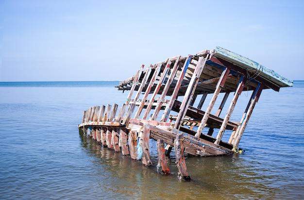 Крушение старой лодки рыбака на море с голубым небом. природа на открытом воздухе. рыболовная жизнь. путешествия летние каникулы концепция.