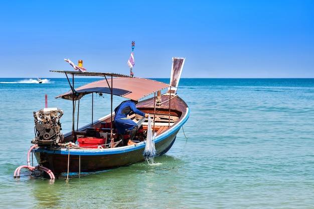 모터 나무 보트에 어부는 낚시 그물을 당겨 화창한 날 푸른 하늘과 바다