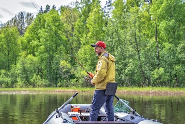 Рыбак на надувной лодке на озере