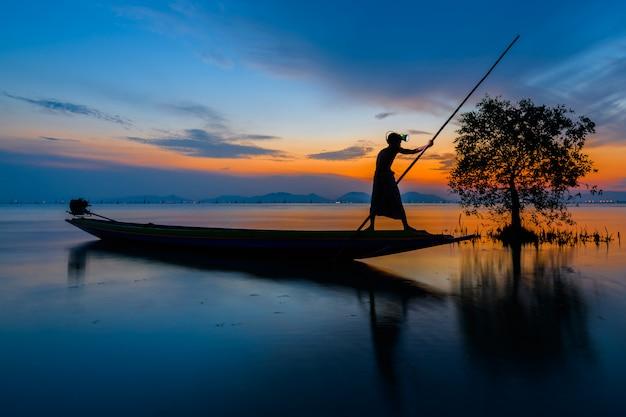 Рыбак на лодке ловить рыбу с восходом солнца