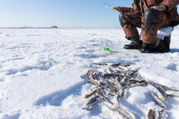 Рыбак на замерзшем море в зимний морозный солнечный день