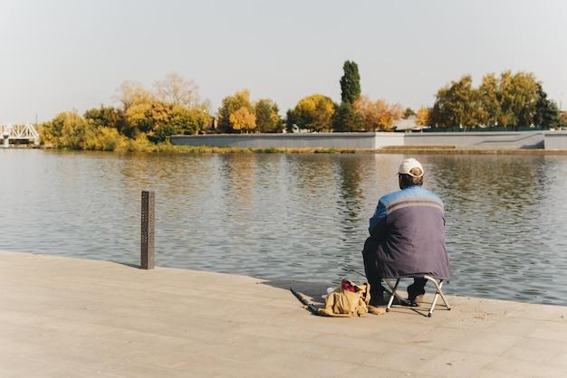 Рыбак на набережной города на фоне осенних деревьев