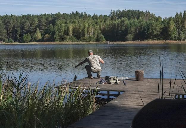 Рыбак на деревянной пристани ловит рыбу на катушку летом